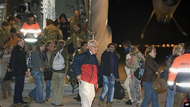 Evacuees from Libya step out of an Italian Air Force C-130 military plane at Rome's Pratica di Mare military airport, February 24, 2011