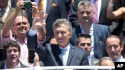 Argentina's President Mauricio Macri waves to followers after he took the oath of office in Congress in Buenos Aires, Dec. 10, 2015.