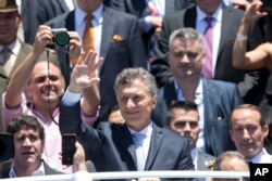 FILE - Argentina's President Mauricio Macri waves to followers as he leaves Argentina's Congress after he was sworn in, in Buenos Aires, Dec. 10, 2015.