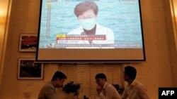港人聚在餐馆里吃喝,同时餐馆内的电视剧正在爆发香港特首林郑月娥在记者会上发表疫情讲话。(2020年3月23日)