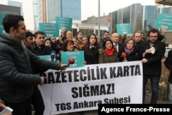 """FILE - Turkish journalists hold a banner reading """"Journalism doesn't fit in the card"""" as they protest the Turkish government cancelling press cards of journalists working for opposition dailies Evrensel and BirGun, in Ankara, Jan. 27, 2020."""