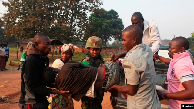 A man wounded in overnight clashes is assisted by peacekeepers and family members in a neighborhood in Bangui, Central African Republic, Dec. 23, 2013.