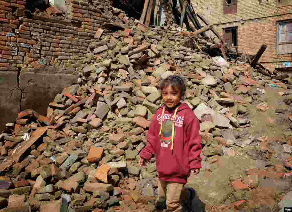 A girl returns to her destroyed home to search for belongings. She later found one of her toys, Sankhu, Nepal, April 29, 2015. (Rosyla Kalden/VOA)