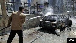 Seorang warga Suriah berusaha memadamkan mobil yang dibakar oleh demonstran anti-pemerintah.di Deraa.