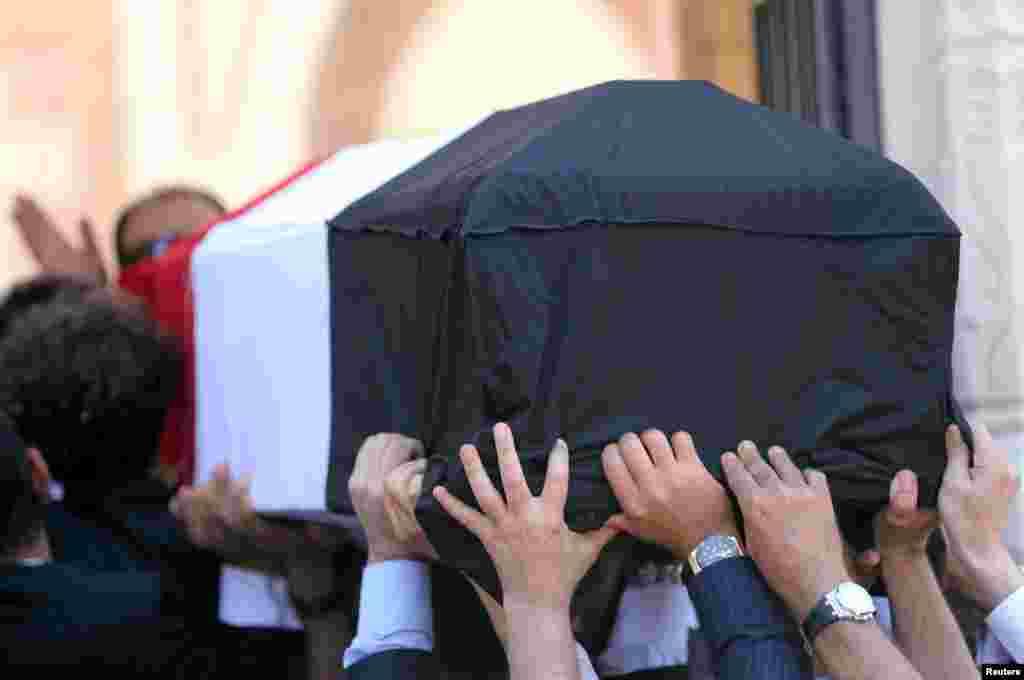 Des proches du défunt et sa famille portent le cercueil du prix nobel en chimie, au Caire, le 7 août 2016.