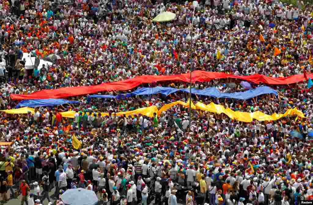 دارالحکومت کراکس میں حزب مخالف کے حامیوں نے پرچم اُٹھا رکھے ہیں۔