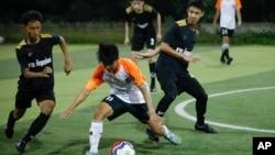 In this July 15, 2018, photo, Wild Boars soccer team, in black, play a local team during a Mae Sai league match in Mae Sai district in Chiang Rai province, northern Thailand.