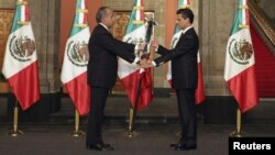 Outgoing leader Felipe Calderon (L) hands the national flag to Mexico's new president, Enrique Pena Nieto, during a midnight ceremony at the National Palace in Mexico City, Dec. 1, 2012.