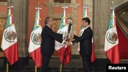 Tổng thống mãn nhiệm Mexico Felipe Calderon (trái) trao quốc kỳ cho tân Tổng thống Enrique Pena Nieto tại buổi lễ giữa khuya ở Dinh Tổng thống ở Mexico City, 1/12/2012