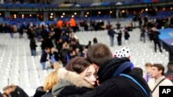 Fans comfort each other after descending onto the playing field in Stade de France stadium at the end of the friendly soccer match between France and Germany in Saint Denis, outside Paris, Nov. 13, 2015, the night of the terror attacks.