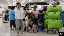 FILE - Passengers wait in line for a flight at Miami International Airport in Miami, Florida, Sept. 27, 2012.