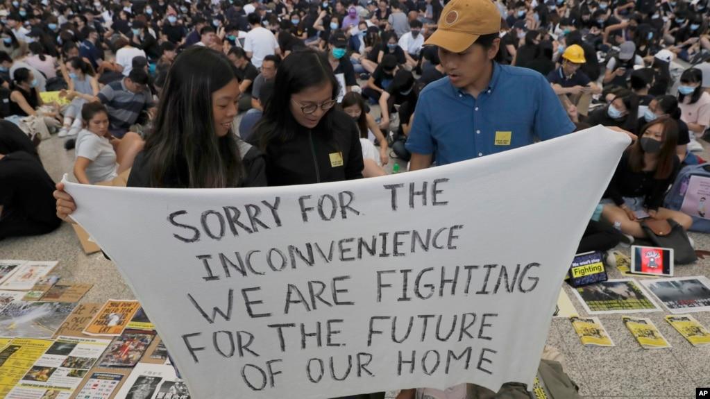 Người biểu tình Hồng Kông với biểu ngữ xin du khách thứ lỗi vì sự bất tiện gây ra từ các cuộc biểu tình.