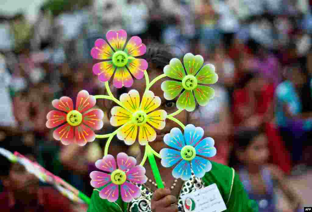 A young Indian girl holds a flower-shaped pinwheel, with each petal representing a child death caused by malnutrition, during a Global Day of Action against Global Hunger event in New Delhi.