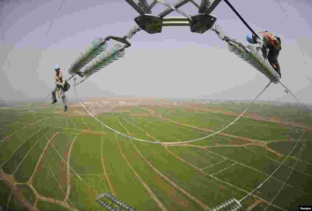 Dua orang teknisi memeriksa tiang listrik yang terletak di tengah lahan pertanian di Chuzhou, provinsi Anhui, China.