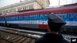 "A railroad worker stands by a train covered with slogans reading ""Kosovo is Serbia,"" written in several languages, departing Belgrade for Mitrovica, Kosovo, Jan. 14, 2017."