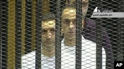 This video image taken from Egyptian State Television shows the sons of Hosni Mubarak, Alaa Mubarak, left and Gamal Mubarak as they stand inside the cage of mesh and iron bars in a Cairo courtroom Wednesday Aug. 3, 2011 as his historic trial began on c