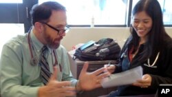 In this Wednesday, Sept. 23, 2015 photo, Dr. Rick Sacra reviews patient cases with Dr. Anna Chon at the Family Health Center in downtown Worcester, Mass., where he advises doctors in training.