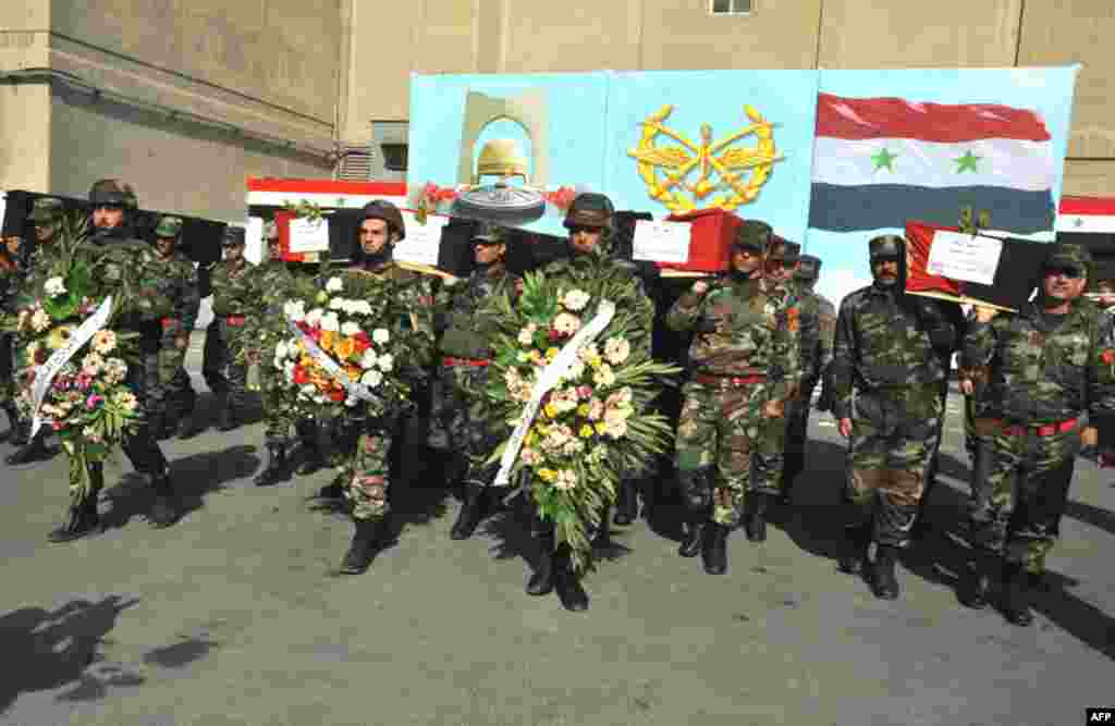 Syrian soldiers carry coffins of their colleagues during a funeral ceremony in Damascus, February 9. (Reuters)