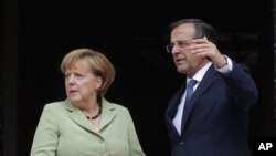 Kanselir Jerman Angela Merkel dan PM Yunani Antonis Samaras berbicara di Athena (9/10/2012). Isu pengampunan utang Yunani menjadi isu penting kampanye politik di Jerman.