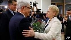 Lithuania's Prime Minister Algirdas Butkevicius (L) and center-left presidential candidate Zigmantas Balcytis (C) congratulate President Dalia Grybauskaite after her winning the presidential election in Vilnius, Lithuania, May 26, 2014.