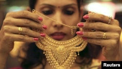 A salesgirl shows a gold necklace to customers at a jewelery showroom in the northern Indian city of Chandigarh, November 11, 2012.