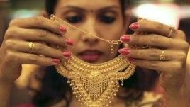 Nhân viên bán hàng cho khách hàng xem một sợi dây chuyền vàng tại một cửa hàng nữ trang ở thành phố phía bắc Ấn Độ Chandigarh.