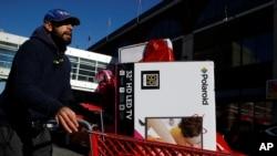 Seorang pria mendorong keranjang penuh barang setelah berbelanja di toko Target pada Black Friday di Brooklyn, N.Y., 24 November 2017.