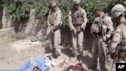 "This image made on Thursday, Jan. 12, 2012 from undated video posted on the Internet on Wednesday, Jan. 11, 2012 by a YouTube user who identified self as ""semperfiLoneVoice"" shows men in U.S. Marine combat gear, standing in a semi-circle over three bodies"