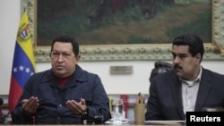 Venezuelan President Hugo Chavez speaks next to Vice President Nicolas Maduro during a national broadcast at Miraflores Palace in Caracas December 8, 2012. Chavez said on Saturday he would undergo another cancer operation in the coming days after doctors