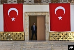 A Turkish parliament security man stands guard next to the broken yellow copper doors laid on the ground at the entrance of the assembly hall at the parliament building which was attacked by the Turkish warplanes during the failed military coup last Friday.