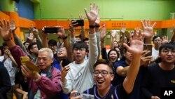 香港选民在他们支持的一名民主派候选人在区议会选举中获胜后举手欢呼。(2019年11月25日)