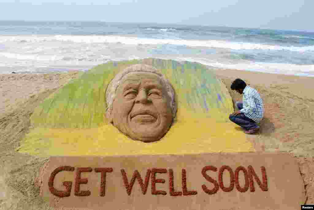 Artist Sudarshan Pattnaik works on a sand sculpture created in the likeness of former South African President Nelson Mandela, in Puri, India, June 9, 2013.