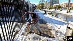 Seorang warga di kota Santiago membersihkan tumpukan salju di depan rumahnya di Santiago, Chile, July 15, 2017.