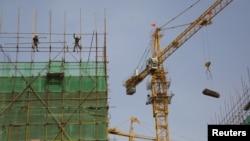 Ouvriers sur un chantier de construction dans une zone industrielle à Beijing, Chine, le 14 Avril 2016.