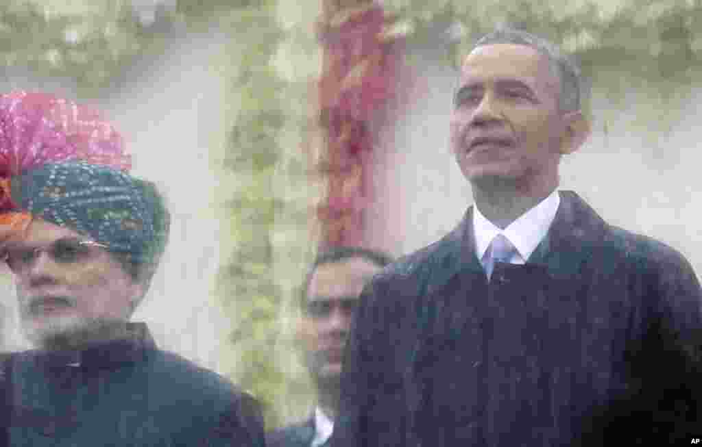 Indian Prime Minister Narendra Modi, left, and U.S. President Barack Obama, right, look out behind a rain covered protective glass to watch the Republic Day Parade in New Delhi, India.