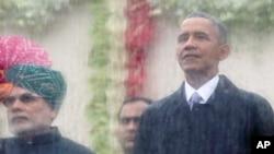 នាយករដ្ឋមន្រ្តីឥណ្ឌា Narendra Modi ខាងឆ្វេង និងលោកប្រធានាធិបតីសហរដ្ឋអាមេរិក បារ៉ាក់ អូបាម៉ា ខាងស្តាំ មើលចេញទៅក្រៅពីក្រោយកញ្ចក់ការពារទឹកដើម្បីទស្សនាក្បួនដង្ហែរនៅក្នុងទីក្រុង New Delhi ប្រទេសឥណ្ឌា កាលពីថ្ងៃទី២៦ ខែមករា ឆ្នាំ២០១៥។