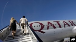 In this Nov. 14, 2011 file photo, visitors walk up stairs to inspect a Boeing 777-200LR aircraft in Qatar Airways livery at the Dubai Airshow in Dubai, United Arab Emirates.