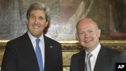 Menlu Inggris William Hague (kanan) menyambut Menlu AS John Kerry dalam pertemuan di London (10/4).
