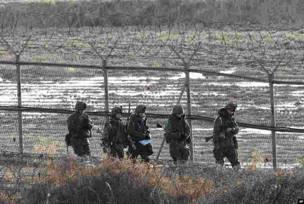 South Korean Army soldiers patrol along a barbed-wire fence near the border village of Panmunjom in Paju, South Korea, March 11, 2013.