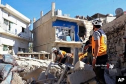 This June 26, 2018, photo, provided by Nabaa Media, a Syrian opposition media outlet, shows civil defense workers and civilians inspecting damaged buildings that were hit by Syrian government forces bombardments, in Daraa, southwestern Syria.