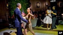 Presiden Barack Obama dan Ibu Negara Michelle Obama menari tango bersama para penari dalam jamuan makan malan di Centro Cultural Kirchner, Buenos Aires, Argentina (23/3).