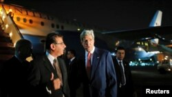 John Kerry ariko yakirwa n'umushikiranganji ajejwe imigenderanire w'igihugu ca Misiri, Nabil Habashi igihe yashika i Cairo italiki 21 z'ukwezi kw'iindwi, umwaka w'2014.