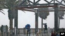 Warga terjebak dalam hujan lebat akibat Badai Tropis Colin di Pantai Clearwater, Clearwater, Florida (6/6).(AP/Chris O'Meara)
