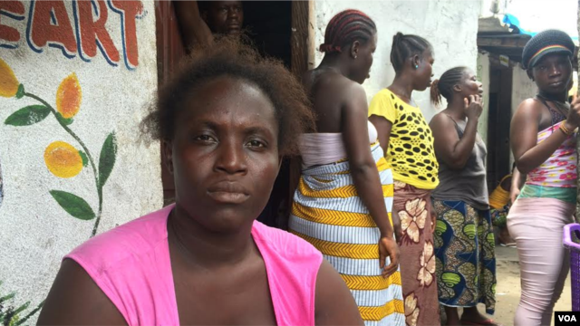 Ebola survivor Finda Fallah sits in front of her new room in West Point, Monrovia, Liberia. As the West African country begins to recover from the crisis, many women are struggling to face a future without their husbands or fathers – the main breadwinners in their families. (Benno Muchler/VOA)
