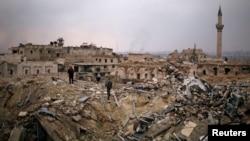 在叙利亚政府控制的阿勒颇区,一名忠于叙利亚总统阿萨德军队的成员和一个平民站在卡尔顿酒店的废墟上。(2016年12月17日)
