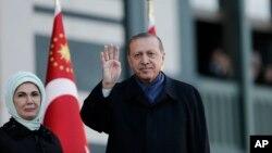 លោក Recep Tayyip Erdogan ប្រធានាធិបតីតួកគី អមដំណើរដោយភរិយារបស់លោកលើកដៃទៅកាន់អ្នកគាំទ្រមុនពេលថ្លែងសុន្ទរកថាមួយថ្ងៃក្រោយការបោះឆ្នោតប្រជាមតិ កាលពីទី១៧ ខែមេសា។
