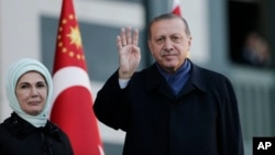 Presiden Turki Recep Tayyip Erdogan dan istrinya, Emine, melambai kepada pendukungnya di Ankara, Senin (17/4).