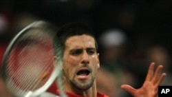 Novak Djokovic of Serbia returns a ball to Gilles Simon of France during their Davis Cup Final match in Belgrade, Serbia, Friday, Dec. 3, 2010.