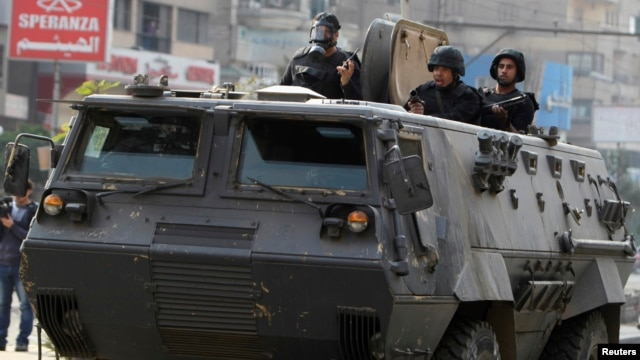 Riot police look from their armoured personnel vehicle during clashes with supporters of Muslim Brotherhood and ousted Egyptian President Mohamed Mursi at Nasr City district in Cairo, Jan. 3, 2014.