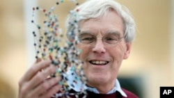 Richard Henderson, one of the 2017 Nobel Prize winners in Chemistry, holds a bacterio rhodopsin model prior to a press conference at the Laboratory of Molecular Biology in Cambridge, England, Wednesday, Oct. 4, 2017.